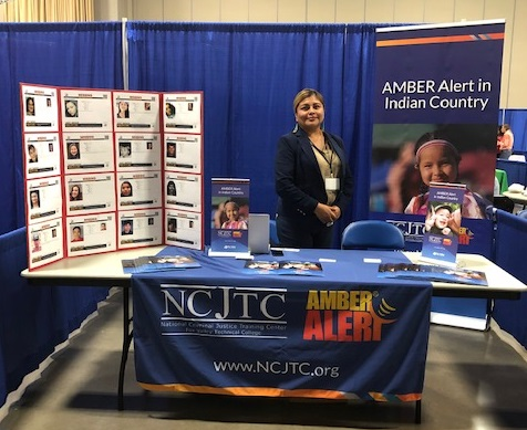 AMBER Alert in Indian Country Female Associate Standing at Information Booth